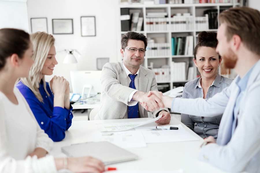Zwei Männer geben sich die Hand in einer Besprechung