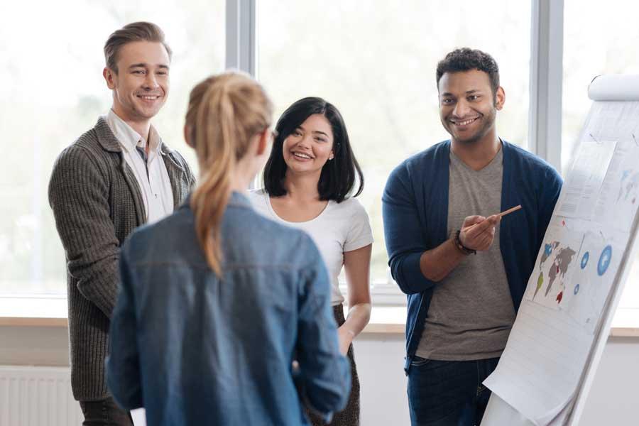 Vier Personen vor einem Whiteboard
