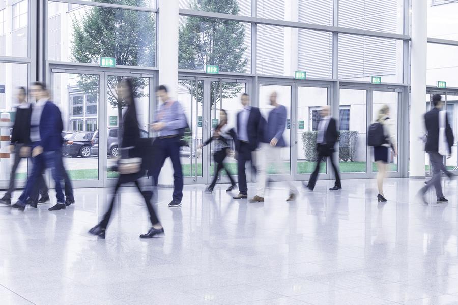 Unscharfes Foto von Personen die durch eine Halle laufen