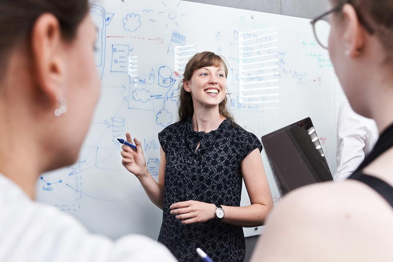 Frau erklärt am Whiteboard