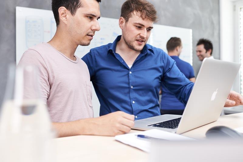 Zwei Mitarbeiter vor einem Laptop