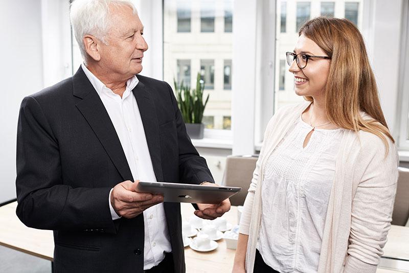 Mitarbeiter hält einer Tablet und redet mit einer Mitarbeiterin