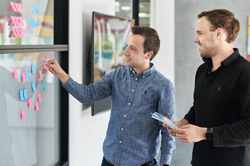 Zwei Männer arbeiten an einer Scheibe mit Post-Its