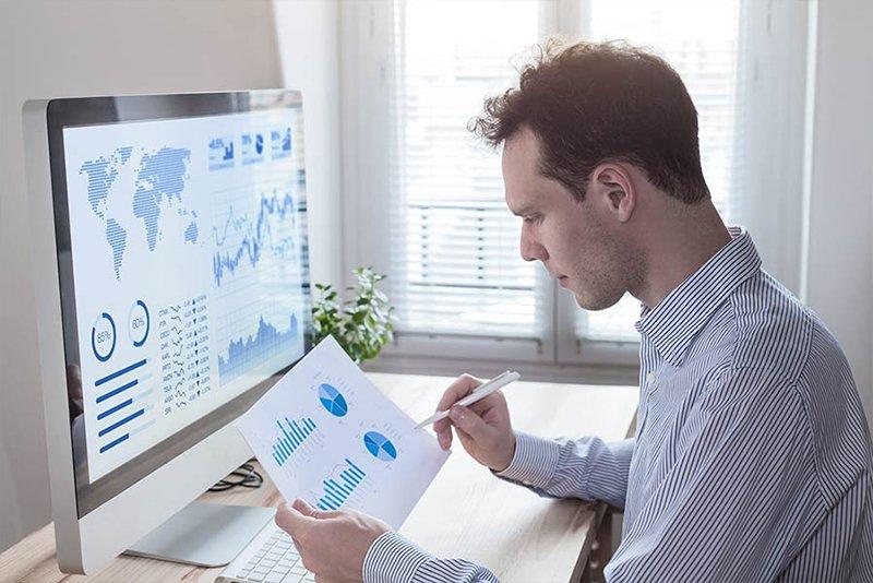 Mann analysiert Bericht vor einem Computer