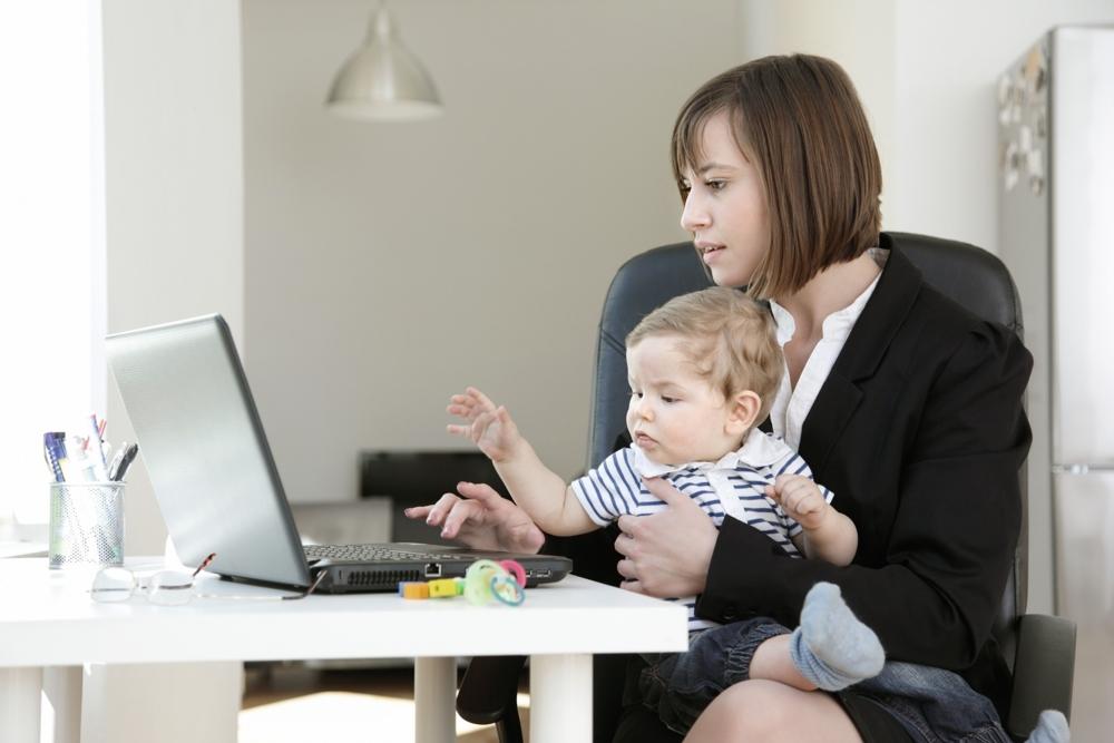 Frau mit Kind arbeitet an einem Computer